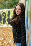 Young model with dark hairs. Graffiti wall. Fall. Young cute girl with long dark hairs. Graffiti wall. Fall. Autumn. Outdoor session Royalty Free Stock Photo