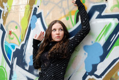 Young model with dark hairs. Graffiti wall. Fall. Young cute girl with long dark hairs. Graffiti wall. Fall. Autumn. Outdoor session Stock Photos