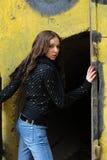 Young model with dark hairs near graffiti wall. Fa. Young cute girl with long dark hairs near open door graffiti wall. Fall. Autumn. Outdoor session Stock Photos
