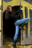 Young model with dark hairs near graffiti wall. Fa. Young cute girl with long dark hairs near open door graffiti wall. Fall. Autumn. Outdoor session Royalty Free Stock Photos