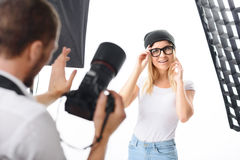 Young model fixes accessories as photographer asks. Photoshoot adjustment. Female perfect-looking model grins charmingly while fixing her accessories stock image