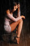 Young model in guipure dress and shoes sits on a rock. Feet in the water under the rain Stock Photography