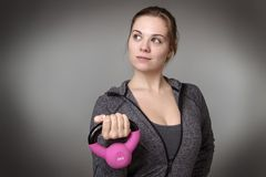 Fitness model on gray background. Young model holding a kettlebell Royalty Free Stock Photo