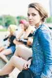 Young model in jeans jacket. Young fashion model posing in jeans jacket with hat. Outdoors, lifestyle Stock Photo