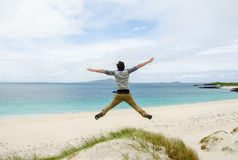 Young model jumping on a sand dune with open arms. White sandy b Royalty Free Stock Photo