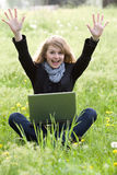 Young model with laptop on green grass Royalty Free Stock Images