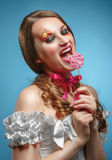 Young model with lollipop. Glossy lips. Fashion makeup. On a blu Stock Photos