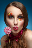 Young model with lollipop. Glossy lips. Fashion makeup. Royalty Free Stock Photo