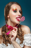 Young model with lollipop. Glossy lips. Fashion makeup. Stock Photo