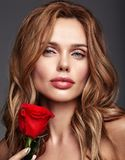Young model with natural makeup and perfect skin. Beauty fashion portrait of young blond woman model with natural makeup and perfect skin with beautiful rose stock photo