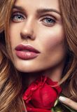 Young model with natural makeup and perfect skin. Beauty fashion portrait of young blond woman model with natural makeup and perfect skin with beautiful rose royalty free stock image