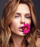Young model with natural makeup and perfect skin. Beauty fashion portrait of young blond woman model with natural makeup and perfect skin with bright flower in stock images