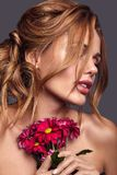 Young model with natural makeup and perfect skin. Beauty fashion portrait of young blond woman model with natural makeup and perfect skin with bright flowers royalty free stock image
