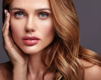 Young model with natural makeup and perfect skin. Beauty fashion portrait of young blond woman model with natural makeup and perfect skin posing in studio royalty free stock image
