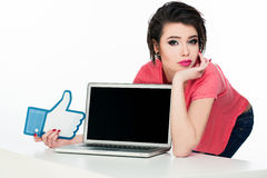 Young model in pink t-shirt with laptop in front of her. Stock Image
