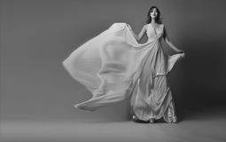 Young model posing in elegant long dress fluttering in the wind. Black-white photo. Stock Images
