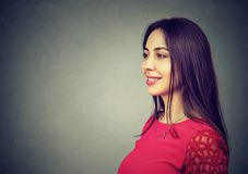 Beautiful brunette woman on gray. Young model in red smiling gently and looking away on gray background stock photo
