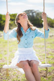 Young model relaxing while sitting on swing Stock Images