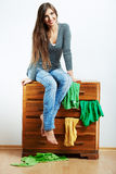 Young model seating at cupboard for clothes. Stock Image