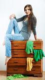 Young model seating at cupboard for clothes. Stock Photo