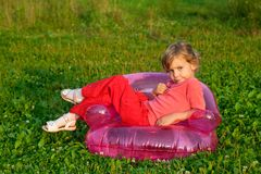 Young model sits in inflatable armchair outdoors Stock Photo
