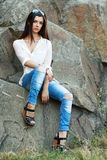 Young model sits on stones Royalty Free Stock Images