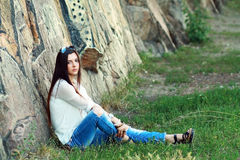 Young model sits on stones Royalty Free Stock Photo