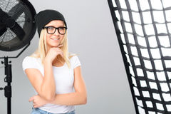 Young model standing beside the spotlight. Natural charm. Young model is smiling thoughtfully and holds index finger at her chin stock photography