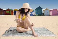 Young model with suntan cream at coast Stock Photography