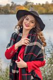 Model teenager posing on the lake in a red coat and black hat. Young model teenager posing on the lake in a red coat and black hat Royalty Free Stock Images