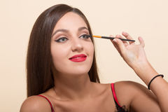 Young model woman doing makeup  on white Stock Photos