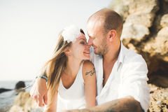 Young models couple posing on the beach with stones Stock Image