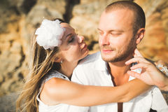 Young models couple posing on the beach with stones Royalty Free Stock Photography