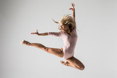 Young modern ballet gymnastics dancer jumping on white background. Young modern ballet dancer jumping on white stock photography