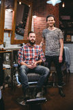 Young modern barber and his handsome content bearded client Stock Photography