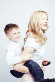 Young modern blond curly mother with cute son together happy smiling family posing cheerful on white background Royalty Free Stock Image