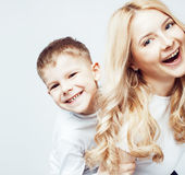Young modern blond curly mother with cute son together happy smiling family posing cheerful on white background Stock Photo