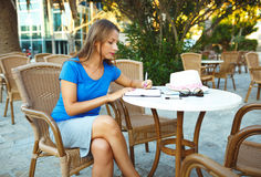 Young modern business woman makes notes in a notebook in a cafe Royalty Free Stock Photo
