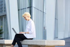 Young modern business woman smiling with laptop outside Royalty Free Stock Photography