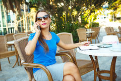 Young modern business woman talking on the phone and makes notes Royalty Free Stock Images