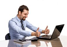Young modern businessman excited with his success giving thumbs up to the laptop Stock Image