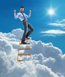 Young modern businessman excited with his success standing at the top of ladder high in the sky Royalty Free Stock Photography