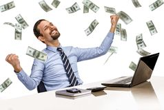 Young modern businessman excited with his success while working with his laptop computer with money rain Royalty Free Stock Images