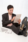 Young modern businessman with laptop and newspaper Stock Photography