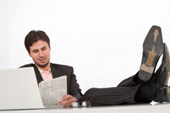 Young modern businessman with laptop and newspaper Royalty Free Stock Photo