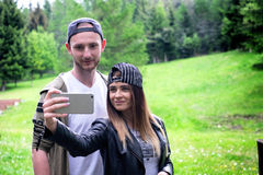 Young, modern couple holding a mobile phones and laughing. Concept of modern relationships. Close up of hipster people sitting on Royalty Free Stock Images