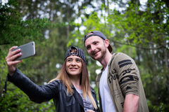 Young, modern couple holding a mobile phones and laughing. Concept of modern relationships. Close up of hipster people sitting on Stock Image