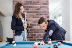 Young modern couple in love playing pool table billiard game stock photography
