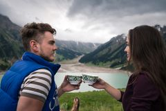 Young modern couple sits near beautiful lake and holds in hands traditional cups. With tea or coffee. Pretty girl drinks with boyfriend. Majestic mountains with royalty free stock photography
