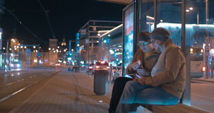 Young modern couple with tablet PC in evening city. Young hipster style couple with pad in the evening city. They talking and coming to tram stop, then sitting stock video footage